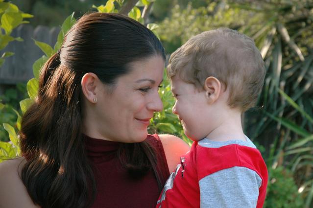 Žena bruneta s culíkem a se synem v náručí někde venku mezi stromy